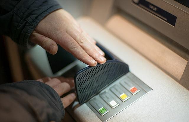 Bild på en person som skyddar sin kod vid uttag av kontanter från en bankomat.